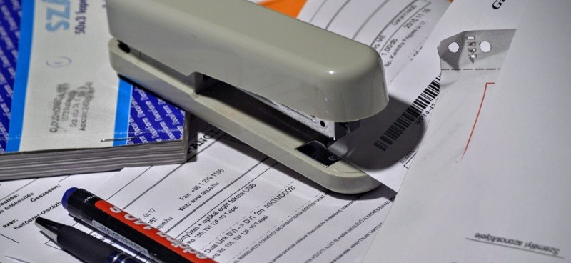 Stapler and pens on a messy pile of paperwork - why you should switch to digital asset management